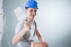 Young tradesman holding a trowel and a brick Stock Photos