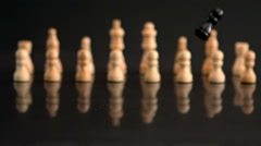 Black chess pieces falling on black background with white pieces Stock Footage