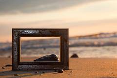 Frame on the beach at sunset. conceptual, memories from holidays. Kuvituskuvat