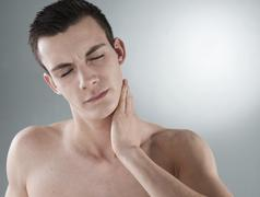 Young man with neck pain Stock Photos