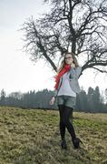 young woman, 25, wearing a red scarf on a meadow in front of a bare tree - stock photo