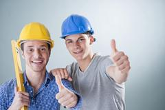 two young tradesmen holding a spirit level, with two thumbs up - stock photo