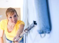Young woman painting a wall Stock Photos