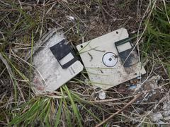 Old discarded floppy discs, data garbage lying in the grass Stock Photos