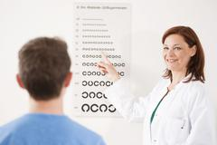 Teenage boy completing an eyesight test with an ophthalmologist Stock Photos