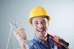 young craftsman holding a wrench - stock photo