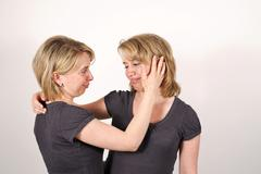 Stock Photo of twin sisters, one comforting the other