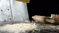 Chef dropping ball of dough on floury surface Stock Footage