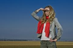 young woman, 25, wearing a red scarf, looking into the distance - stock photo