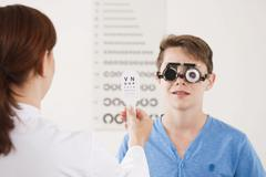 Teenager boy during a vision test at the ophthalmologist Stock Photos