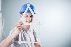 young tradesman holding a folding carpenter's ruler in the shape of a house - stock photo