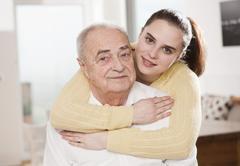 Young woman hugging an elderly man Stock Photos