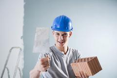 young tradesman holding a trowel and a brick - stock photo