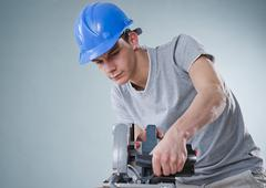 Young tradesman using a jigsaw Stock Photos