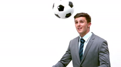 Young businessman heading football away Stock Footage