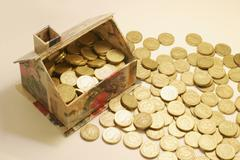 Toy house filled with coins, excess coins aside Stock Photos