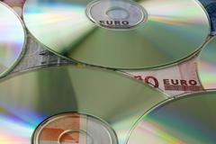 euro-bills and cd-rs - stock photo