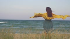 Woman covered with yellow surrounded by sea grass with sea background Stock Footage