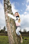Girl, 11 years, climbing on a tree Stock Photos