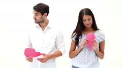 Sad young couple holding two halves of broken heart Stock Footage