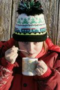 Girl, 9 years old, with woollen hat, drinking tea, outside Stock Photos
