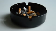 Puting out cigarette in a black ashtray - stock footage