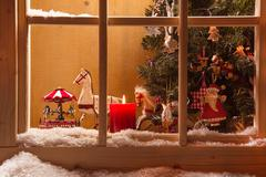 Atmospheric christmas window sill decoration:snow,tre e,candle,rocking horse Stock Photos