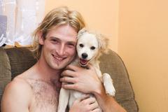smiling blond man, 25 years, and his smiling dog - stock photo