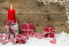 atmospheric christmas card with red burning candle and presents on snowflake - stock photo