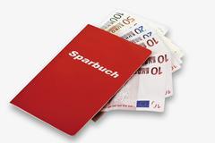 Savings account book with banknotes Stock Photos