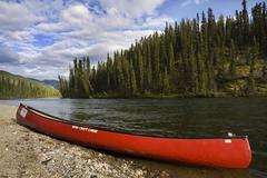 Stock Photo of red canoe on the shore of big salmon river, yukon territory, canada, north am