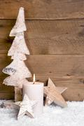 christmas decoration:wooden tree,stars,candle and snow on wooden background - stock photo