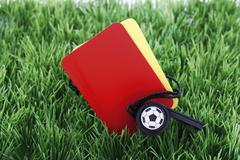 Stock Photo of red and yellow cards with a referee\'s pipe on artificial turf