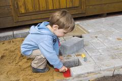 Little builder, a young boy, 20 months old, helping to pave a terrace Stock Photos