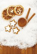 cinnamon stars with dried orange slices and cinnamon sticks on snow - stock photo
