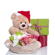 Cuddly teddy bear wearing christmas hat and gift boxes on white background Stock Photos