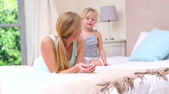 Mother and daughter lying on bed talking Stock Footage
