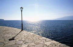 street lamp lit from the back at the waterside promenade of nafplio on the pe - stock photo