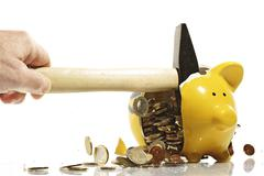 Stock Photo of yellow piggy bank being smashed by a hammer