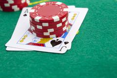 Ace of spades and black jack with red poker chips in the background. Stock Photos