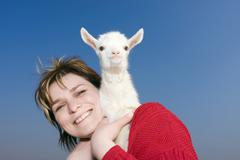 Woman, 36 years, with a white goat kid on her shoulder Stock Photos