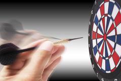 Hand aiming a dart at the dartboard Stock Photos