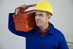 workman wearing a hard helmet holding a toolbox - stock photo
