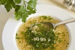 alphabet soup with parsley and noodle letters, a spoon and a serviette in a s - stock photo