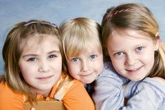 Three children, 6, 4 and 11 years, huddled together Stock Photos