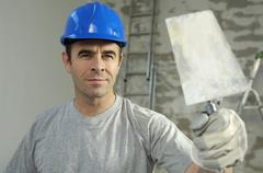 workman wearing a hard hat, holding a brick trowel - stock photo