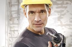 workman wearing a hard hat, holding a drill - stock photo
