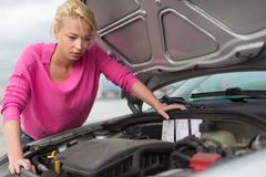 Woman inspecting broken car engine. - stock photo