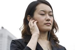 young woman with a walkman, ipod, mp3-player, tokyo, japan, asia - stock photo