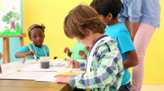 Cute pupils painting pictures with teacher Stock Footage